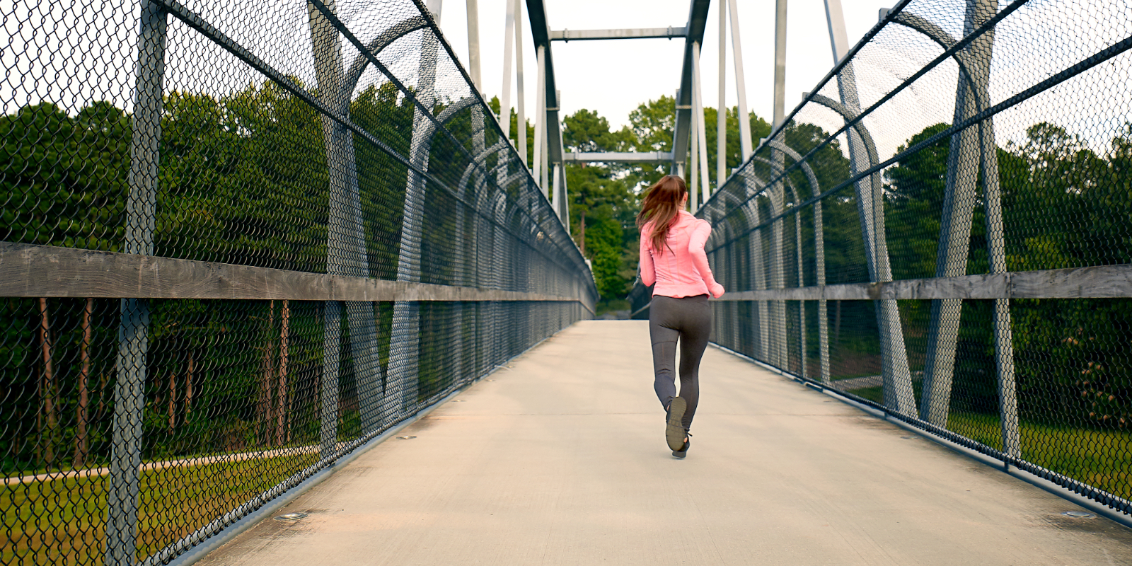 A woman wearing athletic wear runs across a bridge utilizing Sof Sole® insoles, socks and shoe care.
