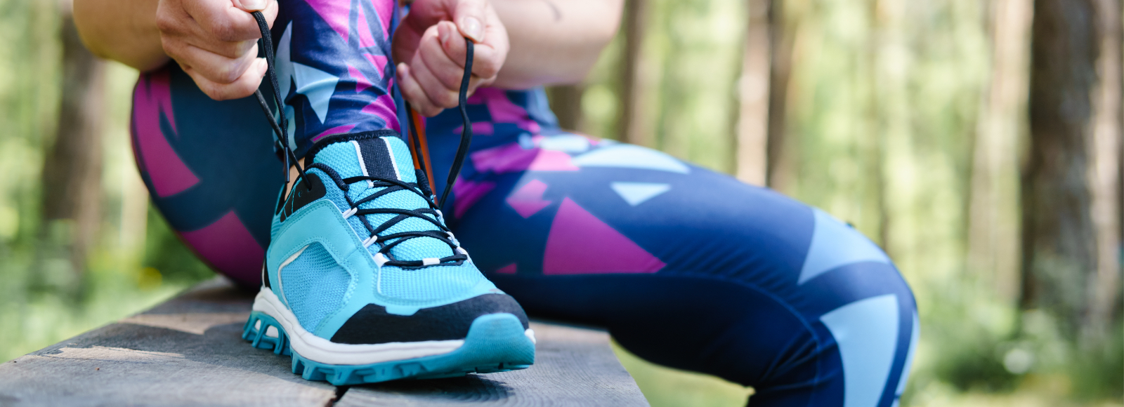 A woman in brightly colored running tights laces up her running shoes with Sof Sole® shoe laces.