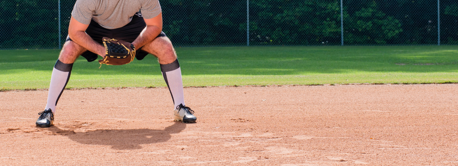 A man stands ready with a baseball glove on a baseball field wearing Sof Sole® baseball stirrup socks.