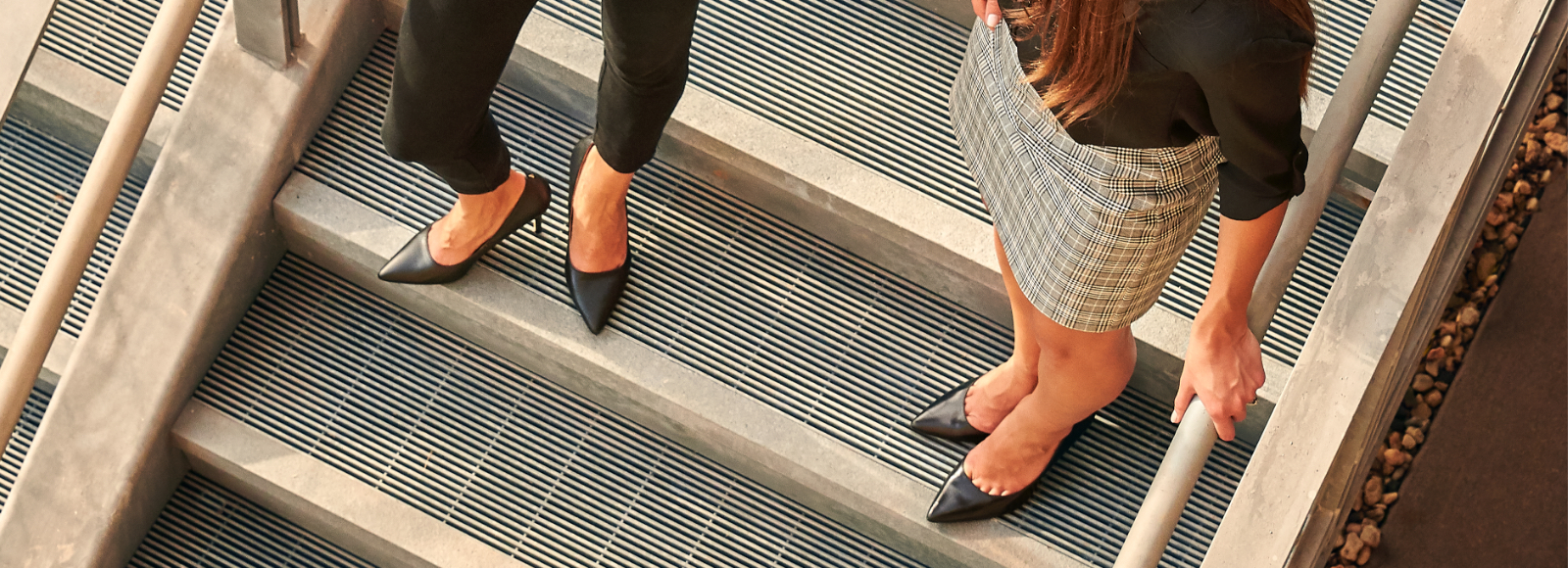 Aerial view of two women talking on stairs while wearing Sof Sole® comfort insoles and black leather heels.