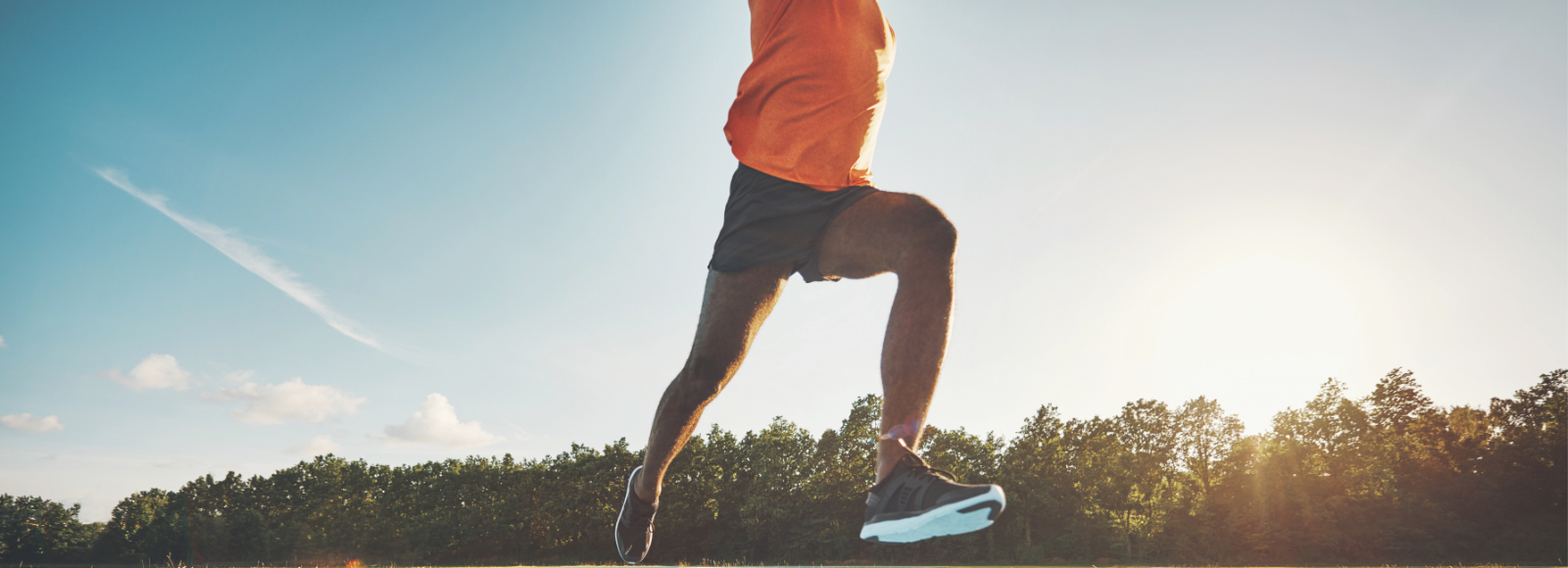 A man in athletic wear leaps forward with the sun in the background using his Sof Sole® performance insoles.