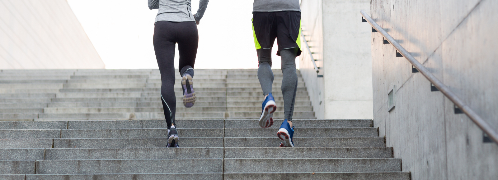 A man and woman in athletic wear run up stairs side by side while using Sof Sole® support insoles.