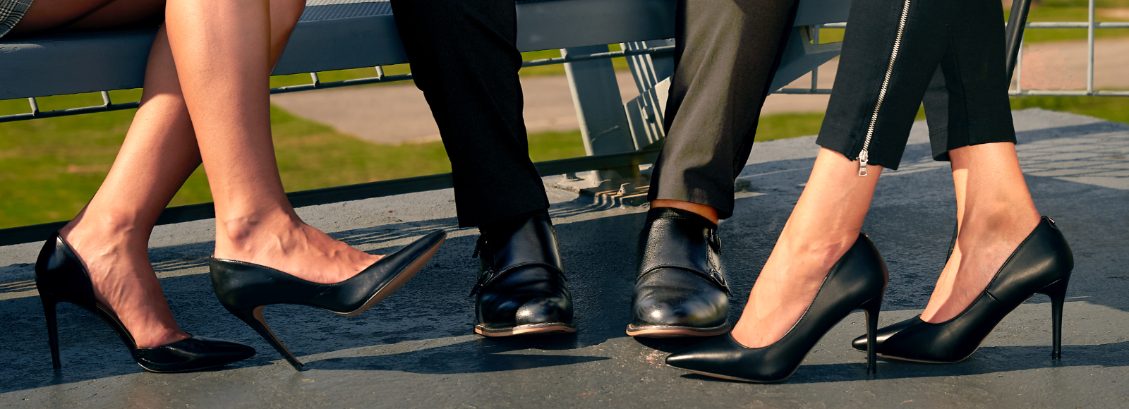Focused on their feet, two women and a man sit on a bench in black leather shoes treated with Sof Sole® shoecare.