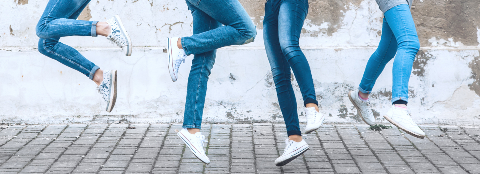 Four people mid-jump in blue jeans and white shoes kept clean with Sof Sole® clean products.