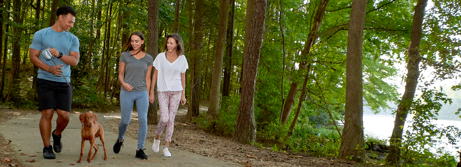 A man walks his dog alongside two women on a forest trail while wearing Sof Sole® comfort socks.