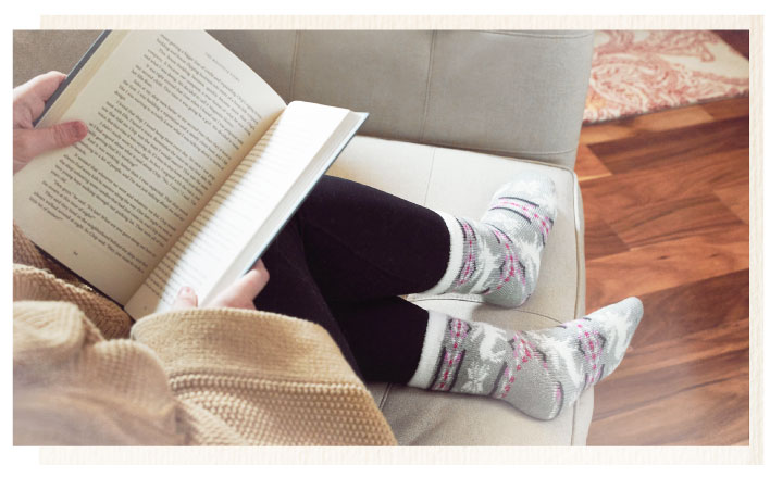 woman curled up on couch reading a book in Sof Sole Fireside socks