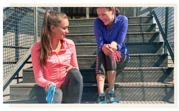 mother and daughter in workout gear, sitting on step holding Sof Sole laces
