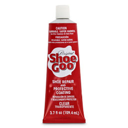 Red tube of Shoe Goo on white background.